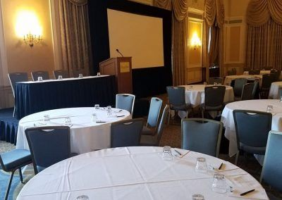 A ballroom space that is set for a conference with round tables and a stage that has a podium, a large screen and a rectangle table.