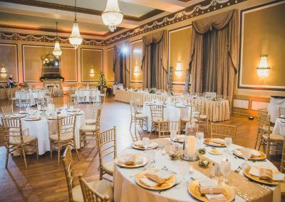 A ballroom in the hotel that is called the Gold Ballroom with wooden floors and gold chairs with antique chandeliers. A grand mirror is against the golden walls.