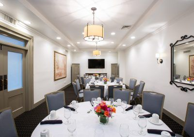 Three round tables with blue chairs around them sit in a private dining room space. THe tables have brightly colored floral displays and coffee mugs sit on the tables.