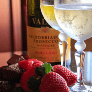 Two glasses of wine are filled halfway and strawberries are placed in front of the glasses with a bottle of wine in the background.