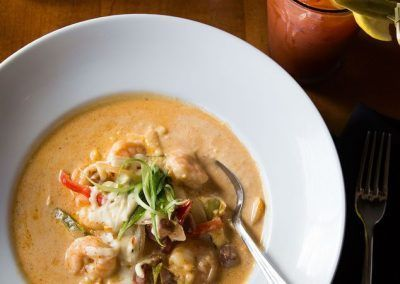 a plate of shrimp and grits with a bloody mary and a cup of coffee.