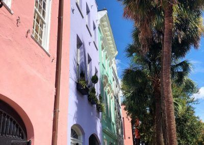 Pink, purple, blue color houses line a street as a lady in a pink outfit walks on the sidewalk towards the camera. Tall palm trees line the other side of the sidewalk and the sky is bright blue and its sunny out.