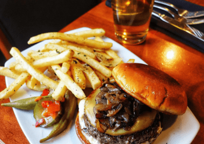 A burger with sautéed mushrooms and a white cheese. Yellow crispy fries sit next to the burger and green okra and pickles garnish the plate.