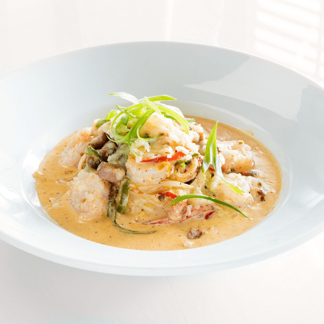 A bowl of shrimp and grits with a creamy orange sauce and green onions sit on top.