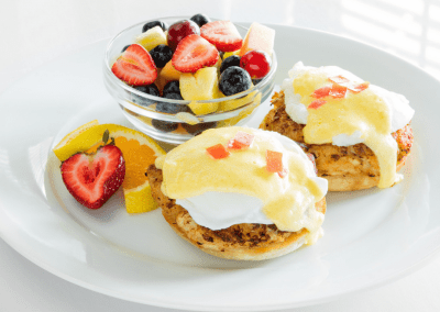 A plate of eggs benedict with yellow hollandaise sauce and a cup of fruit filled with red strawberries, yellow pineapple and blueberries.