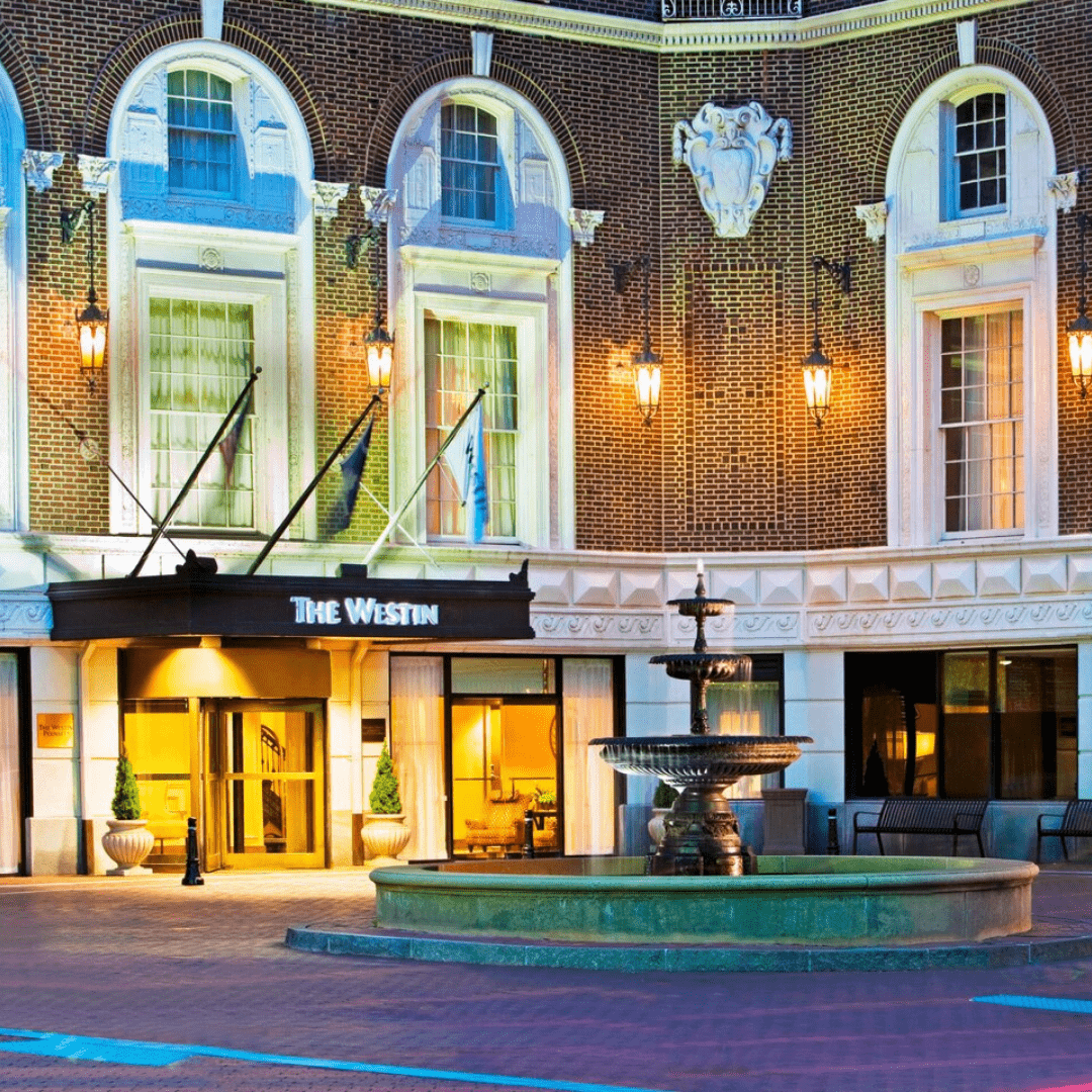 The façade of the Westin Poinsett hotel. A fountain sits in front of the doors and it is a grand, brick building with white molding and three flags fly above the westin signage.